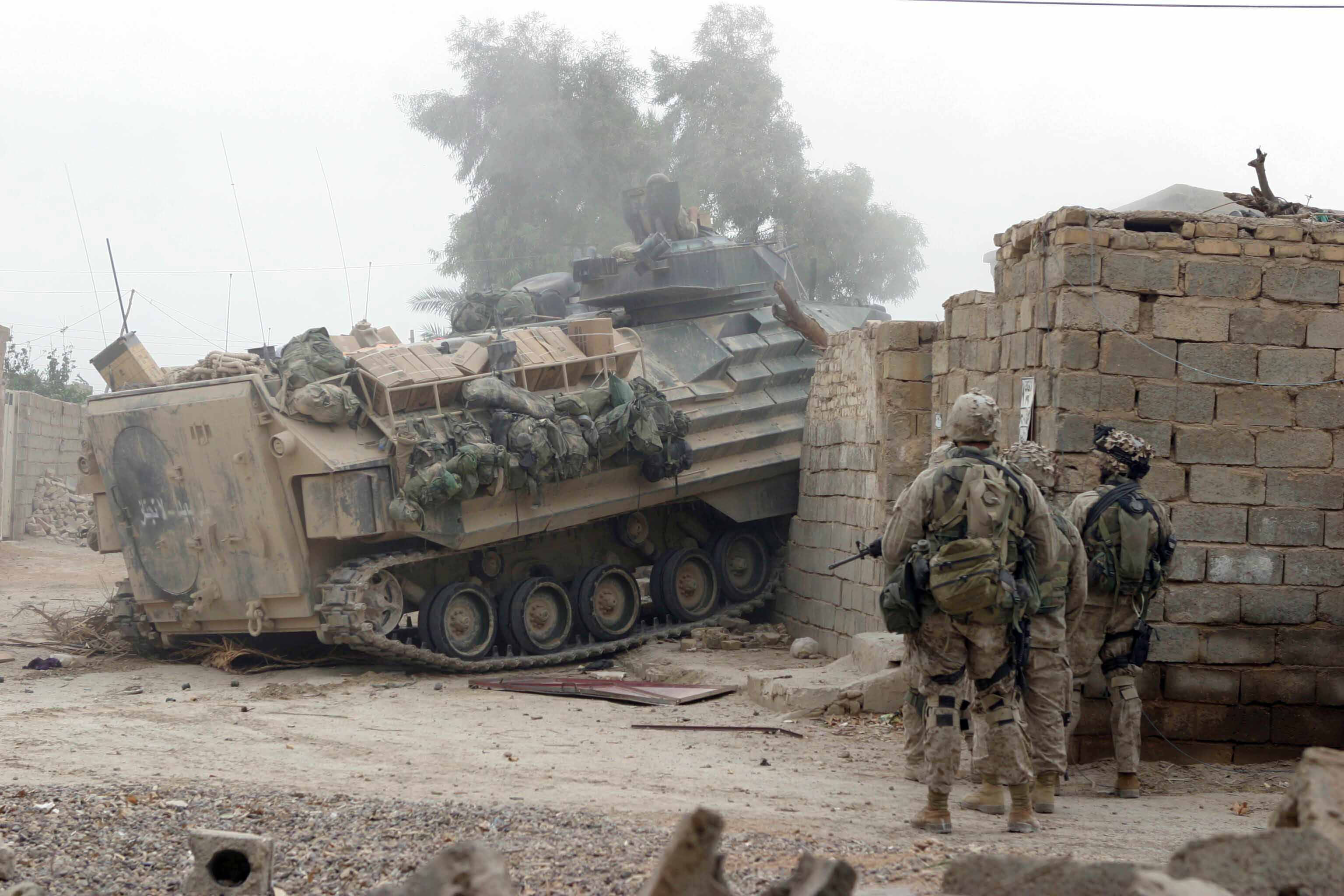 17 Nov 2004: An Amphibious Assault Vehicle (AAV) drives through a wall and locked gate to open a path for Marines from 2nd Platoon, India Company, 3rd Battalion, 1st Marines, 1st Marine Division to gain entrance to a building that needed to be cleared.  Operation Al Fajr is an offensive operation to eradicate enemy forces within the city of Fallujah in support of continuing security and stabilization operations in the Al Anbar province of Iraq by units of the 1st Marine Division.   Official USMC Photograph by LCpl Ryan L Jones